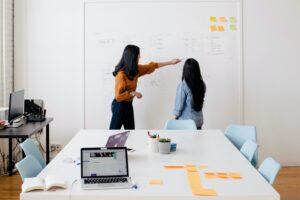 Zwei Frauen besprechen Notizen auf einem Whiteboard.